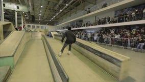 Rullskateboradåkaren gör plugghäst på språngbrädan med arg fot extremt trick Konkurrens i skatepark lager videofilmer