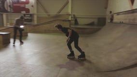 Rullskateboradåkaren gör snedsteget på staketet i skatepark språngbräda cameraman challenge konkurrens arkivfilmer