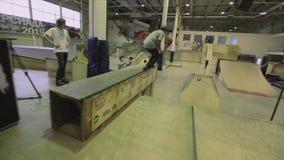 Rullskateboradåkaren hoppar från en språngbräda på andra extremt trick Konkurrens i skatepark arkivfilmer
