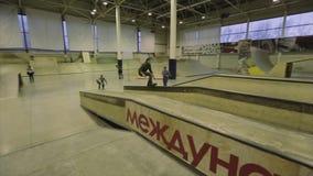 Rullskateboradåkaren hoppar från en språngbräda på andra stanna extremt Konkurrens i skatepark stock video