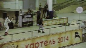 Rullskateboradåkaren hoppar, griper foten i luft Ritt på staketet, avverkning på magen Konkurrens i skatepark stock video