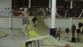 Rullskateboradåkaren hoppar, griper foten i luft Vänd över i luftritt på språngbrädan Konkurrens i skatepark arkivfilmer