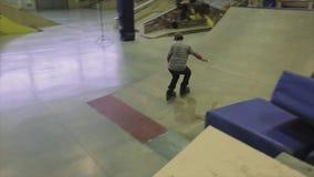 Rullskateboradåkaren hoppar handlagfoten i luft språngbräda Extremt jippo Konkurrens i skatepark lager videofilmer