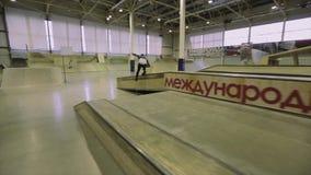 Rullskateboradåkaren hoppar handlagfoten i luft språngbräda extremt trick Konkurrens i skatepark lager videofilmer