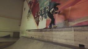 Rullskateboradåkaren hoppar på kanten av språngbrädan med arg fot på konkurrens i skatepark challenge arkivfilmer