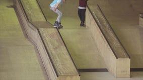 Rullskateboradåkaren i exponeringsglas rider på kanten av språngbrädan på strid i skatepark challenge konkurrens stock video