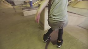 Rullskateboradåkaren i hatt gör extrem tillbaka flip och rider på kanten av språngbrädan i skatepark challenge stock video