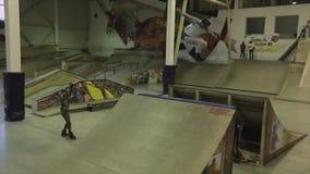 Rullskateboradåkaren i lock gör dubbelt flip i luft språngbräda extremt trick Konkurrens i skatepark stock video