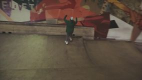 Rullskateboradåkaren i lock rullar på den höga kanten av språngbrädan på konkurrens i skatepark challenge stock video