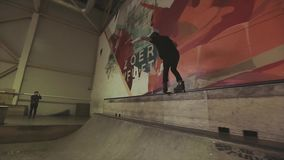 Rullskateboradåkaren rullar på kanten av språngbrädan på konkurrens i skatepark Hopphandlagfot i luft arkivfilmer