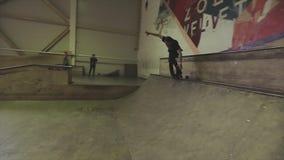 Rullskateboradåkaren rullar på kanten av språngbrädan på konkurrens i skatepark Jippo på en fot challenge lager videofilmer