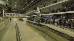 Rullskateboradåkareplugghäst på staketet med arga ben språngbräda extremt trick Konkurrens i skatepark stock video