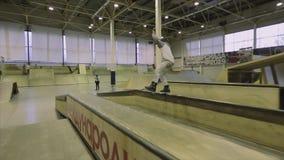 Rullskateboradåkareplugghäst på staketet på en fot språngbräda extremt trick Konkurrens i skatepark lager videofilmer