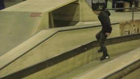 Rullskateboradåkareplugghäst på staketet på en fot språngbräda extremt trick Konkurrens i skatepark stock video