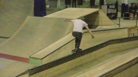 Rullskateboradåkareritt på staketet med arga ben språngbräda extremt trick Konkurrens i skatepark arkivfilmer