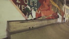 Rullskateboradåkarerullar på kanten av språngbrädan trycker på väggen på konkurrens i skatepark jippo challenge lager videofilmer