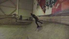 Rullskateboradåkarerulle på kantsprångbrädan på konkurrens i skatepark Jippo med arga ben challenge stock video