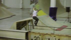 Rullskateboradåkaresnedsteg på staketet med korsad fot, ritt på språngbrädan Konkurrens i skatepark lager videofilmer