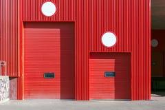 Rullslutareport på den röda väggen av fördelningslagret Arkivbild