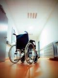 Rullstol i mitt av ett långt tomt sjukhushall Arkivbild