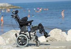 Rullstolen för rörelsehindrat folk på bryggan av vaggar vid havet Arkivfoton