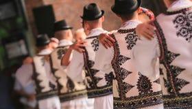 Rumänische folklorische unerkennbare Tänzer auf Stadium Nationale Kostüme stockfotografie
