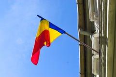Rumänische wellenartig bewegende Flagge auf dem Gebäude gegen den blauen Himmel lizenzfreies stockfoto