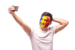 Rumänisches Fußballfannehmen selfie Foto mit Telefon auf weißem Hintergrund lizenzfreies stockfoto