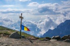 Rumänsk flagga överst av Bucegi berg, Rumänien Arkivbilder