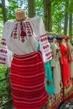 Rumänska traditionella dräkter på skyltdockor och hängare som visas ou arkivbild