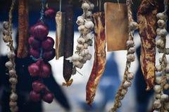 Rumänskt klassiskt kött Utomhus- Meathanging: bacon, vitlök och lökar arkivbilder