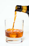 Rum. Pouring into glass of ice stock image