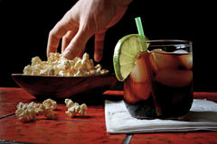 Rum and coke with hand in popcorn Royalty Free Stock Image