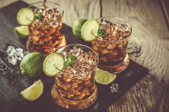 Rum and cola cocktail in glasses. Rustic wood background Royalty Free Stock Images