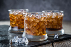 Rum and cola cocktail in glasses. Rustic wood background Royalty Free Stock Photos