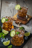 Rum and cola cocktail in glasses. Rustic wood background Royalty Free Stock Image
