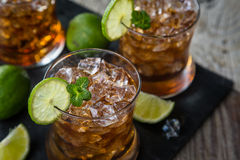 Rum and cola cocktail in glasses. Rustic wood background Royalty Free Stock Photo