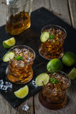 Rum and cola cocktail in glasses. Rustic wood background Stock Image