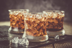 Rum and cola cocktail in glasses. Rustic wood background Stock Photo