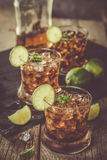 Rum and cola cocktail in glasses. Rustic wood background Stock Photos