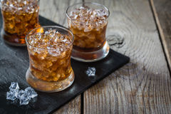 Rum and cola cocktail in glasses. Rustic wood background Stock Images