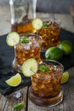 Rum and cola cocktail in glasses. Rustic wood background Stock Photography