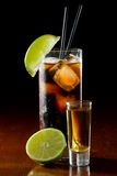 Rum and cola. Cuba libre, rum and cola cocktail served in a tall glass with a lime garnish and a shot of rum on the side royalty free stock image