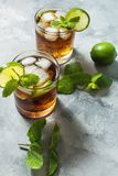Rum and cola. Cuba Libre drink with lime and ice on rustic concrete table.  stock photography