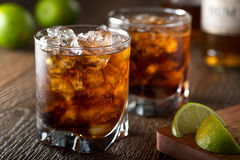 Rum and Cola. Cuba libre with lime and ice on a wooden bar top Royalty Free Stock Images