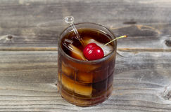 Rum and Cola with large red cherry Stock Photos