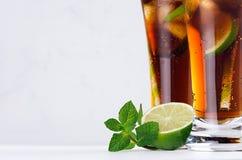 Rum e cola freschi del cocktail in vetri lunghi eleganti con le bolle ed i cubetti di ghiaccio nell'interno bianco della luce mor Fotografia Stock