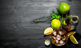 Rum with ice , mint and fresh lime. On a black wooden background Stock Photography