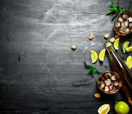 Rum with ice , mint and fresh lime. On a black wooden background Royalty Free Stock Photo