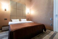 Rum med en dubbelsäng, nattduksbord, och en vit dörr, gråa väggar och en laminatdurk På varje sida av sängen på vägglamen arkivfoton